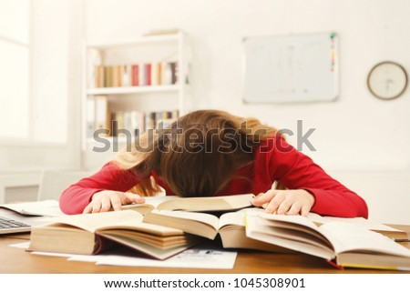 Tired girl studying at working table. Exhausted female student reading books and working on laptop. Education and technology concept #1045308901