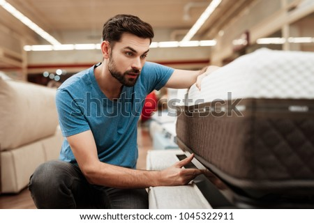 Handsome bearded man is testing mattress in furniture store. Orthopedic mattress for a healthy posture. Checking mattress in furniture store. #1045322911