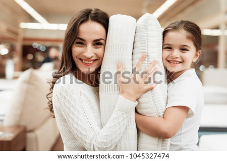 Smiling little girl with beautiful mother hugs pillows in store of orthopedic mattresses. Testing softness of pillow. Check softness of orthopedic pillow. #1045327474