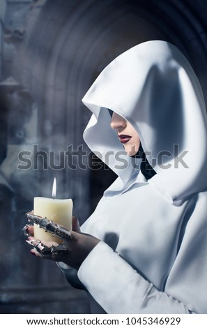 Sorceress in white hooded cloak holding a burning candle standing in the castle. Profile view photo.