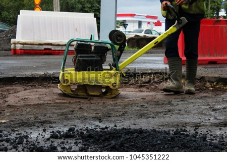 A road construction worker compacts the soil with a compact vibroplate before asphalting a problematic swampy section of the road. Russia, entry in the city of Gatchina #1045351222