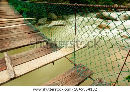 Damaged suspended, wooden bridge over tropical river Mexican jungle. Long exposure makes a dreamy ambiance. #1045354132