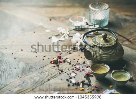 Traditional Asian tea ceremony arrangement. Iron teapot, cups, dried rose buds and candles over wooden table background, selective focus, copy space #1045355998
