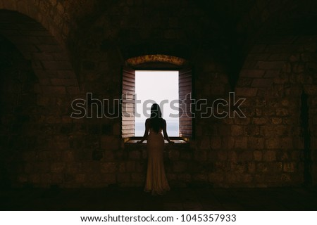 woman looking at the window in old fort. Dubrovnik, Lovrijenac #1045357933