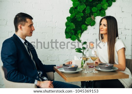 smiling couple having dinner and drinking white wine at date in restaurant #1045369153