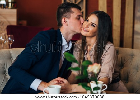 a couple dinners in a restaurant a man kisses a woman #1045370038