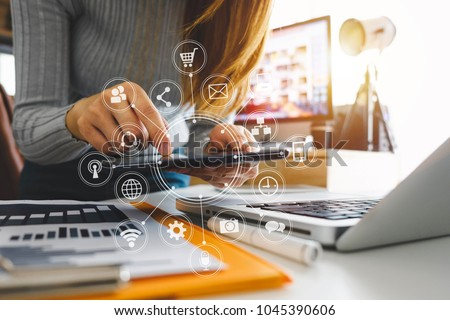 designer woman using smart phone for mobile payments online shopping,omni channel,sitting on table,virtual icons graphics interface screen in morning light  #1045390606