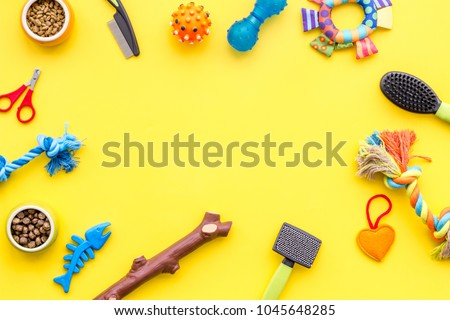 grooming equipment with brushes and toys for care and training pet yellow background top view mock up #1045648285