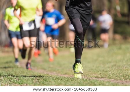 Marathon running race, people feet on grass road #1045658383