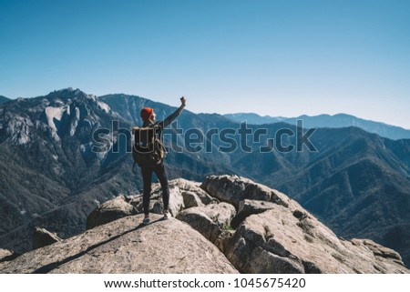 Young female explorer with touristic backpack making selfie on smartphone camera posing on rock cliff in mountains, hipster girl wanderlust on hiking tour taking picture on cellular for blogging