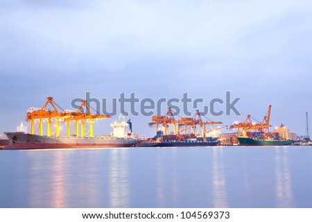 Big Container Cargo freight ship with working crane in shipyard at night for Logistic Import Export background #104569373