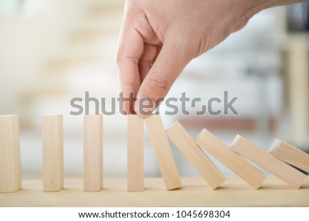 Man hand is holding the wooden block of tumbling tower to stop falling for business concept #1045698304