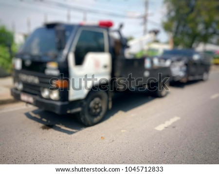 Blured police department tow truck an accident on the road during the day to prevent the danger of duplications #1045712833