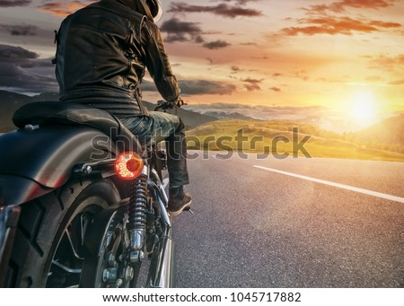 Motorcycle rider ready for drive in Alps, beautiful sunset dramatic sky. Travel and freedom, outdoor activities #1045717882
