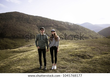 happy couple holding hands and enjoying a walk through grass land #1045768177