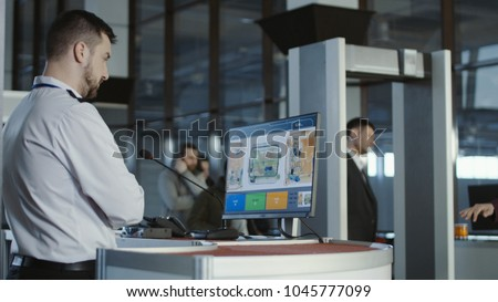 Man in uniform standing at counter at checking point and watching at monitor with x-ray of luggage. #1045777099