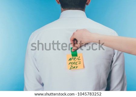 cropped shot of woman putting note with april fools day lettering on males back, april fools day concept Royalty-Free Stock Photo #1045783252