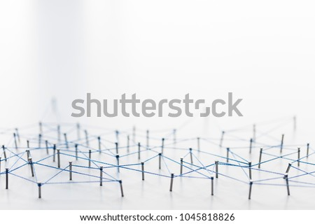 A large grid of pins connected with string. Communication, technology, network concept #1045818826