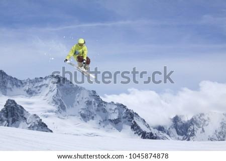 Skier jump in the mountains. Extreme ski sport. Freeride. #1045874878