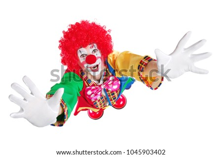 Clown in a white studio stretching his hands to the camera #1045903402