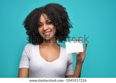 Young pretty African American millennial woman with natural curly hair smiling holding a blank white poster on a blue isolated background.