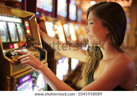 Asian woman gambling in casino playing on slot machines spending money. Gambler addict to spin machine. Asian girl player, nightlife lifestyle. Las Vegas, USA. #1045958089