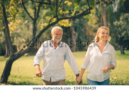 senior couple smiling and relaxing in a park on a sunny day #1045986439