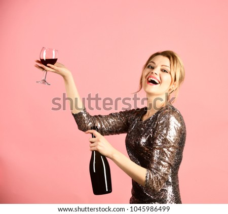 Lady holding glass and bottle of red Italian wine. Winetasting or party concept. Woman with smiling face drinks expensive cabernet or merlot. Girl in shining dress with alcohol on pink background. #1045986499