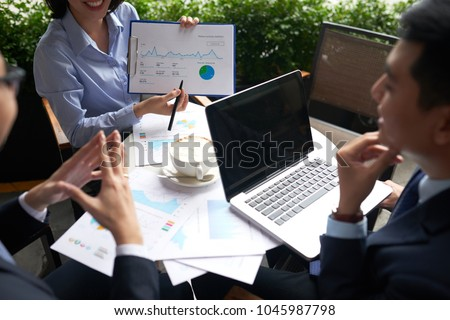 Cheerful business lady explaining information in financial report to coworkers #1045987798