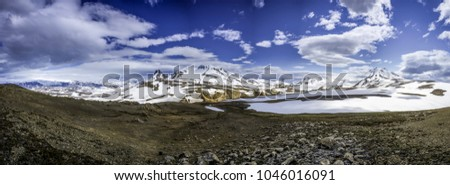 Wide-angle panorama photo of Landmannalaugar rainbow mountains covered by snow. Colorful hills and mountains of famous and popular icelandic trek. Mountain peaks and blue sky in summer day on Iceland.