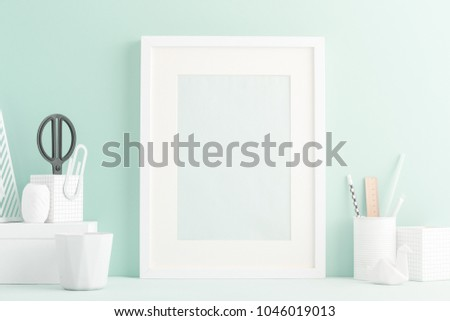 Mock up white frame, books, office supplies and houseplant on well arranged desk. Bright pastel colors. #1046019013
