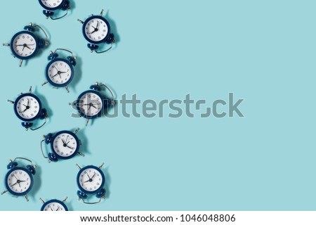 Flat lay retro beautiful new alarm clock on blue color background. Pattern. Copy space