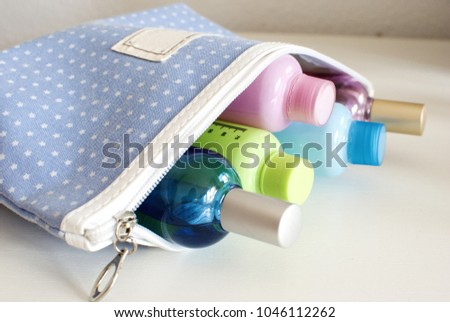 Blue travel toiletry bag with travel toiletries, small plastic bottles of hygiene products and perfume. Royalty-Free Stock Photo #1046112262