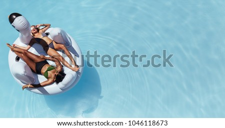 Top view of female friends wearing bikini lying on an inflatable toy in pool. Woman sunbathing on floating pool inflatable toy. #1046118673