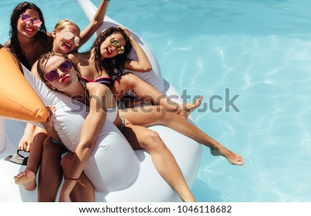 Attractive young women floating together on a big inflatable swan in pool. Woman making a pout with her friends relaxing in an inflatable toy in pool. Royalty-Free Stock Photo #1046118682