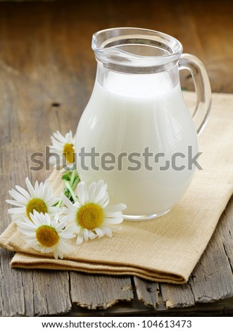 pitcher of milk on a wooden table wish  daisy , rustic still life #104613473
