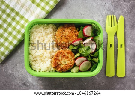 Lunch box with boiled rice, chicken cutlets ans radush salad. #1046167264