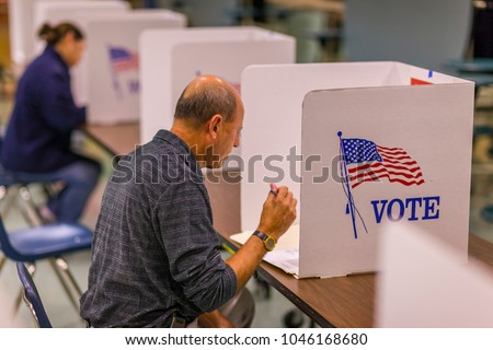 FAIRFAX COUNTY, VIRGINIA, USA - NOVEMBER 4, 2008: Voter at polls during presidential election, using paper ballots. #1046168680