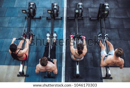 Group of sporty muscular people are working out in gym. Cross fit training. Paddling training apparatus. Top view of four sportsmen are rowing together. Royalty-Free Stock Photo #1046170303