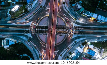 Top view over the highway, motorway at night, Aerial view interchange of a city, Expressway is an important infrastructure. #1046202154