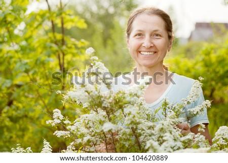 Happy mature gardener in Meadowsweet plant at garden #104620889