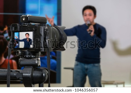 Professional digital Mirrorless camera with microphone on the tripod recording video blog of asian Speaker on the stage seminar, Camera for photographer or Video and Technology Live Streaming concept Royalty-Free Stock Photo #1046356057