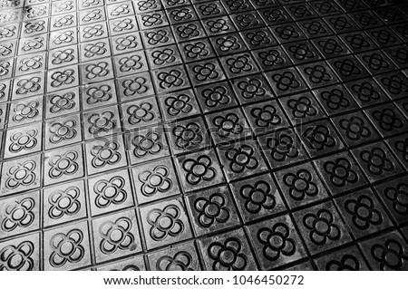 Barcelona wet flower paving. Street floor background. Black and white photo.