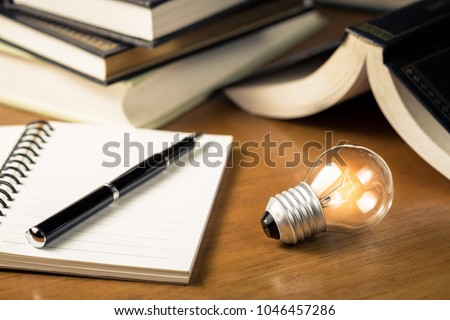 Small light bulb glowing on the desk, with notebook and many books on background, reading and writing idea concept Royalty-Free Stock Photo #1046457286