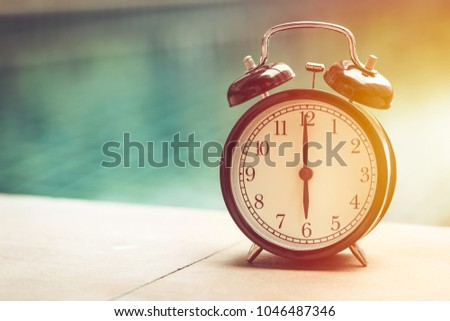 afternoon times clock with blur water park background vintage colortone #1046487346
