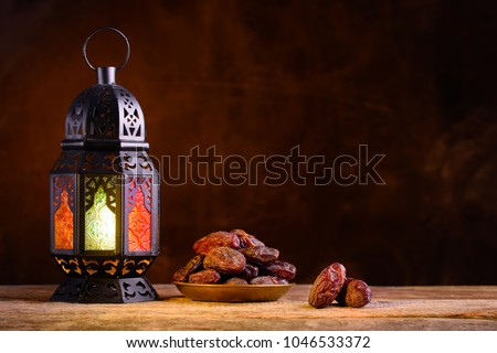 Ramadan concept. Dates close-up in the foreground. Ramadan Lantern on a wooden table. Textured yellow wall background. Space for text on the right.  #1046533372