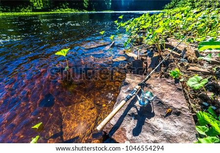 Fishing rod on river bank scene #1046554294