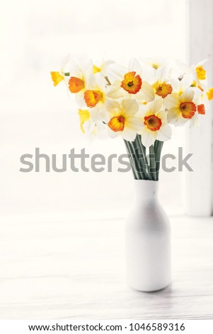 beautiful fresh daffodils in light in stylish modern vase on white wooden table. hello spring image with bright yellow flowers on rustic wood  at window light. floral greeting card