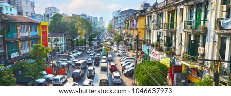 YANGON, MYANMAR - FEBRUARY 14, 2018: The obstructed traffic along the Anorata Road, one of the main avenues of Chinatown (Tayoke Tan), on February 14 in Yangon. #1046637973