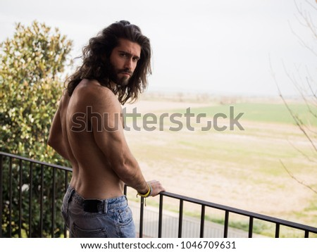 Man with long hair and no upper cloth on a roof #1046709631